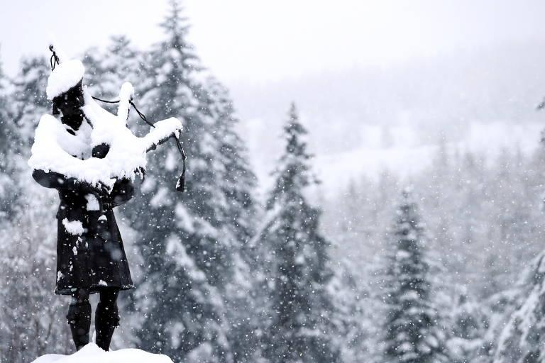 Estátua de um flautista fica parcialmente branca por causa da neve; atrás, árvores também está cobertas de neve