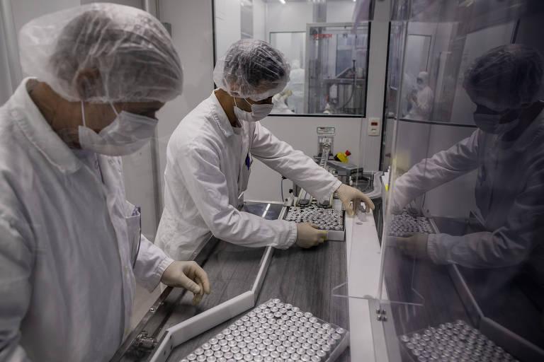 Após a selagem dos frascos, funcionários na linha de produção da Coronavac organizam os vidros em bandejas para depois fazer o controle de qualidade