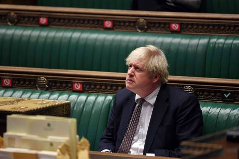 A handout photograph released by the UK Parliament shows Britain's Prime Minister Boris Johnson attending Prime Minister's Questions (PMQs), in a socially distanced and hybrid session of the House of Commons, in central London on December January 13, 2021. - Britain will make appointments for coronavirus vaccinations available 24 hours-a-day