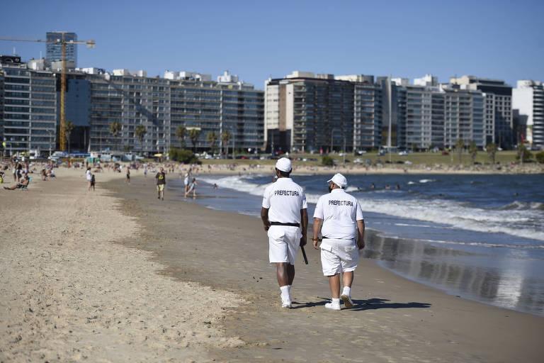 Oficiais da prefeitura patrulham a praia Pocitos, em Montevidéu, para prevenir aglomerações