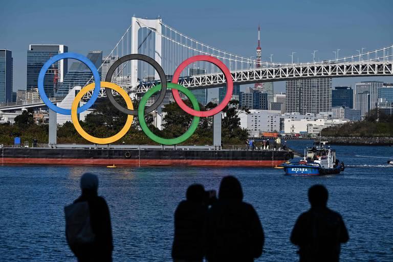 Pessoas observam os cinco anéis olímpicos