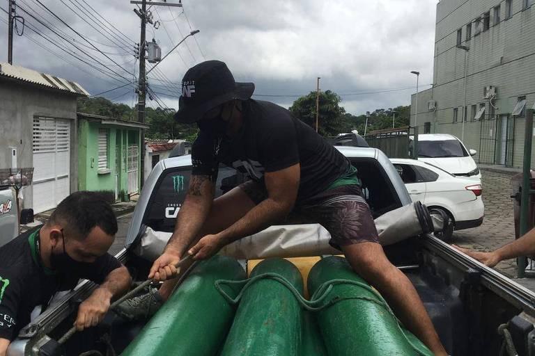 homem está em cima de pilha de cilindros de oxigênio em caminhão