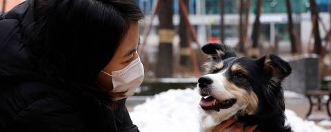 Moon Sae-mi pets her dog Godot as they demonstrate Petpuls, an AI-powered smart dog collar, in Seoul, South Korea, January 11, 2021. Picture taken on January 11, 2021.   REUTERS/Kim Hong-Ji ORG XMIT: HFS-KHJ03