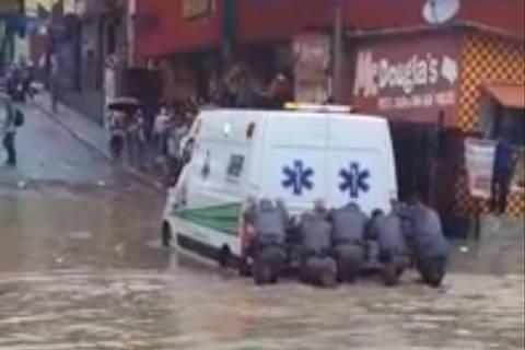 Policiais empurram ambulância presa em enchente em SP. Foto: Reprodução.