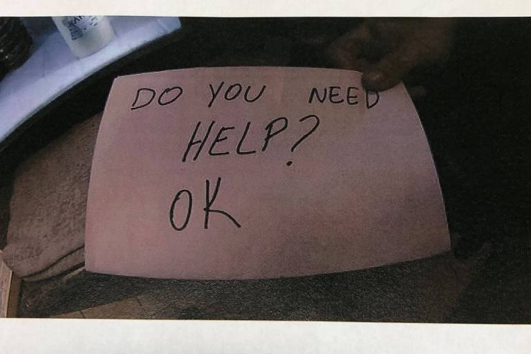 O cartaz usado pela brasileira para perguntar se a criança precisava de ajuda