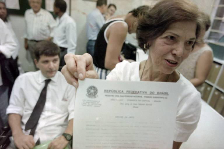 Mulher em pé exibe documento