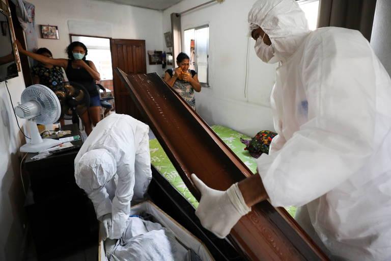 Trabalhadores do SOS Funeral se preparam para retirar o corpo de Adamor Mendonça, 75. Segundo parentes, ele havia morrido de Covid-19 em casa após não encontrarem vaga nem oxigênio nas unidades de saúde de Manaus