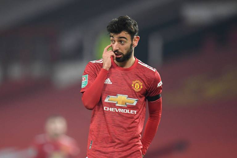 Jogador com uniforme vermelho leva um dedo ao olho