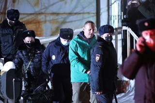 Russian opposition leader Alexei Navalny is escorted by police officers after a court hearing, in Khimki