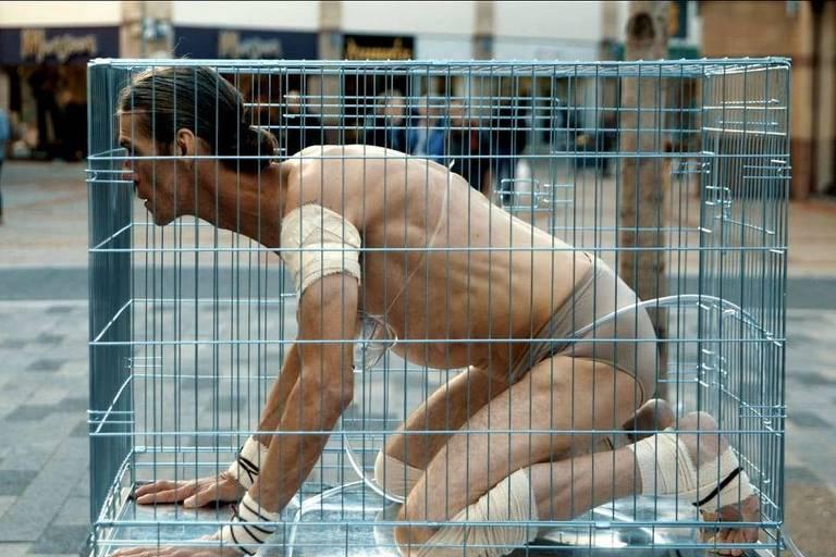 Homem seminu dentro de uma gaiola em um local público