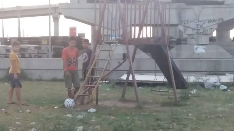 Crianças brincam em terreno com ponte inacabada ao fundo