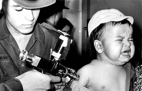 Dezembro de 1975  -  Criança é vacinada através de uma pistola de vacinação, um mecanismo de ar comprimido, que, quando acionado por um pedal, proporcionava uma poderosa fonte de pressão. Sem o uso de agulha, a administração percutânea da vacina se dava através de um fluxo de alta pressão.eficiente por permitir a vacinação de muitas pessoas rapidamente, a pistola era um dispositivo caro e exigia constante manutenção, além de uma capacitação especial para os profissionais. (Foto: Folhapress)