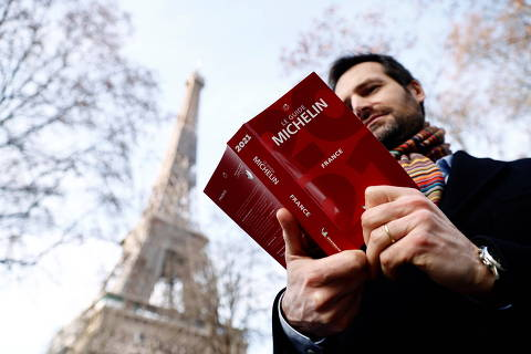 Gwendal Poullennec, International Director of Michelin Guides poses holding a copy of the Michelin Guide 2021 before the ceremony to award stars to French restaurants, which have been closed for months due to restrictions against the spread of the coronavirus disease (COVID-19), in Paris, France, January 18, 2021.    REUTERS/Christian Hartmann ORG XMIT: gggchm01