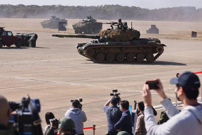 Pessoas de costas para a câmera tiram fotos de tanques de guerra avançando sobre planície deserta