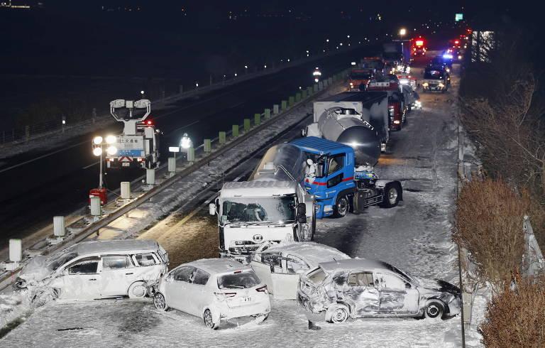 Imagem aberta mostra carros batidos, atravessados na pista, e engavetamento em rodovia coberta por neve