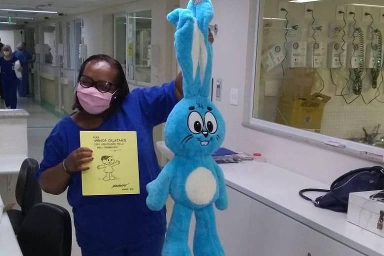 A enfermeira Monica Calazans com um Sansão de pelúcia e quadro enviado por Mauricio de Sousa em sua homenagem