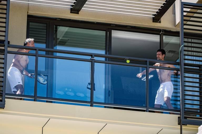 Dois homens sem camiseta jogam tênis em sacada de quarto de hotel