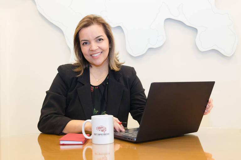 Mulher branca está sentada e sorri em frente a um notebook, caneca e bloco de anotações. Os objetos estão sobre uma mesa de madeira. O fundo da imagem é branco
