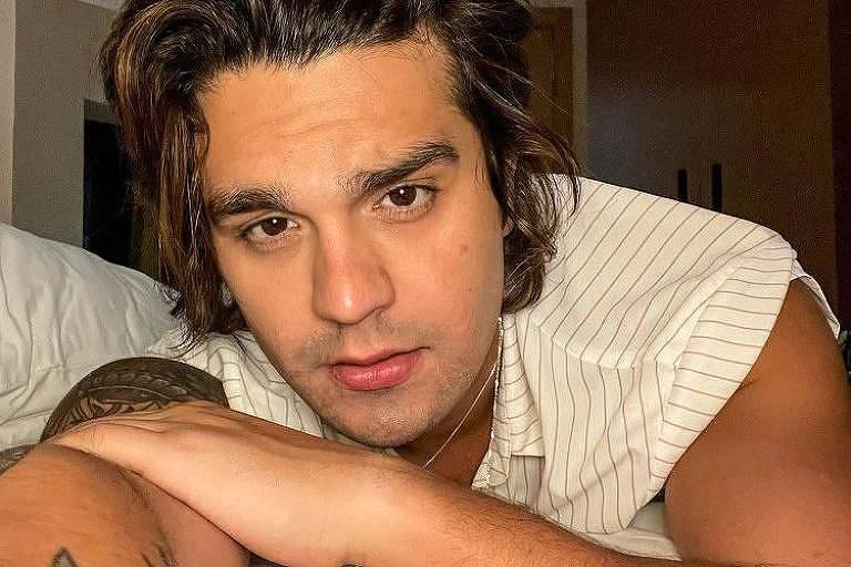 O cantor Luan Santana em foto postada em sua rede social. Ele está deitado na cama e olha para a câmera.