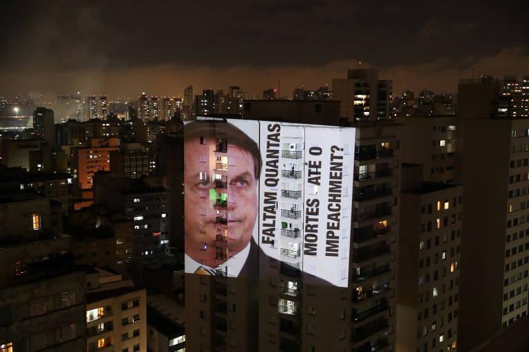 """Projeção em prédio no centro de São Paulo mostra o presidente Jair Bolsonaro ao lado da frase """"Faltam quantas mortes até o impeachment?"""""""