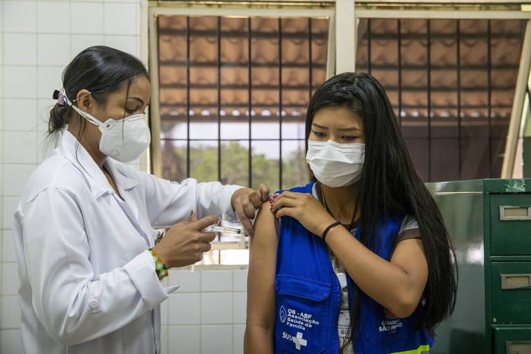 A indígena Iasmin Pires, da aldeia Krukutu (sul da capital paulista) é vacinada contra a Covid-19