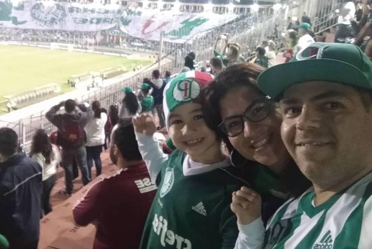 Homem, mulher e o filho deles olham para foto durante jogo em estádio de futebol