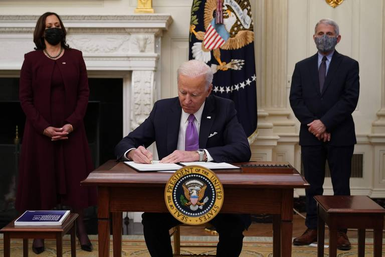 O presidente dos EUA, Joe Biden, assina as novas ordens contra o coronavírus acompanhado de sua vice, Kamala Harris, e do infectologista Anthony Fauci