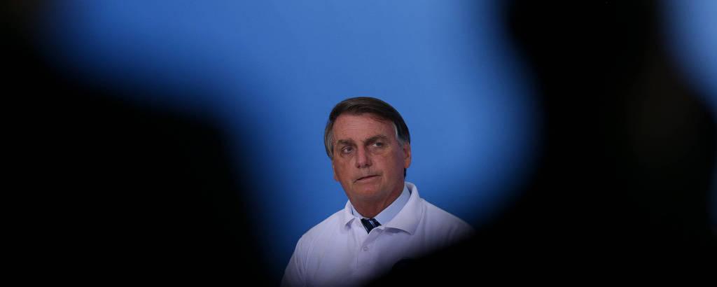 Bolsonaro sentado ao fundo, com sombras de pessoas no primeiro plano