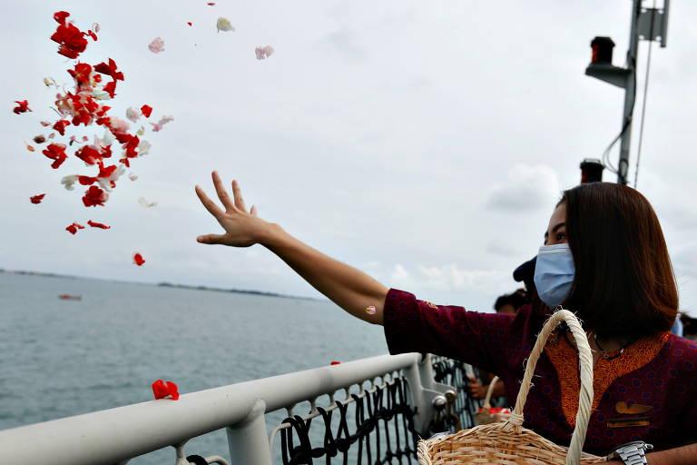 Mulher segura cesta e estende o braço jogando pétalas ao mar