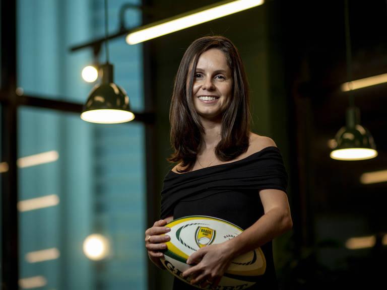 Mulher com roupa escura segura bola de rúgbi em escritório iluminado