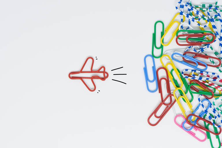 Foto com clipes coloridos, há um avião formado por clipes vermelhos, saindo de um outro grupo de clipes coloridos