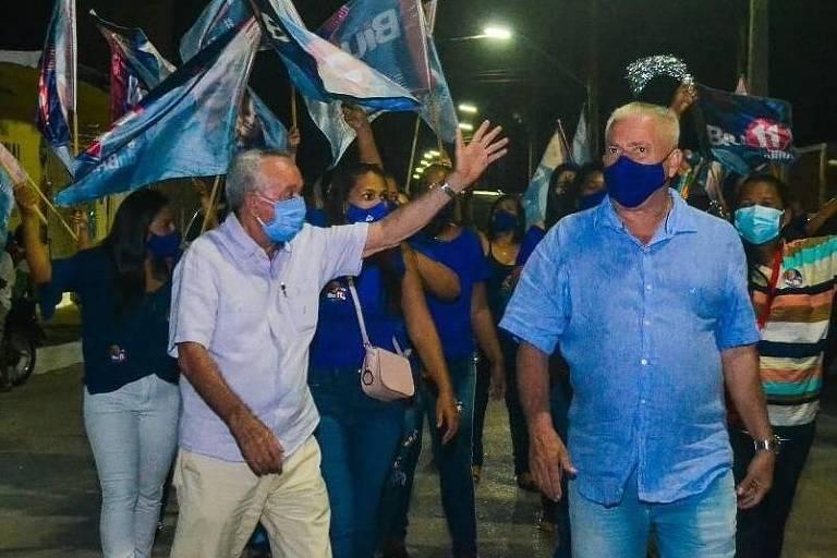 Homem idoso de máscara acena durante caminhada com cabos eleitorais e bandeiras