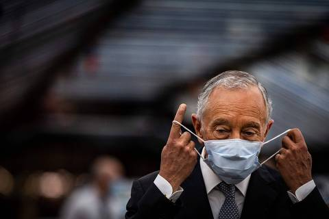 (FILES) In this file photo taken on May 13, 2020 Portuguese President Marcelo Rebelo de Sousa adjusts his face mask during a visit to the Volkswagen Autoeuropa car factory in Palmela, 30 kms south of Lisbon, on May 13, 2020. - The first round of the presidential election will be held on January 24, 2021. (Photo by CARLOS COSTA / AFP)