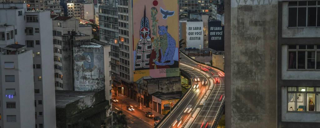 Vista do elevado Presidente João Goulart, que nasceu como Costa e Silva, em 1971, mas foi sempre o Minhocão; é uma foto noturna, vemos a estrutura serpentear entre prédios, alguns dos quais exibem grafites coloridos; os faróis dos carros deixam marcas de luz na pista