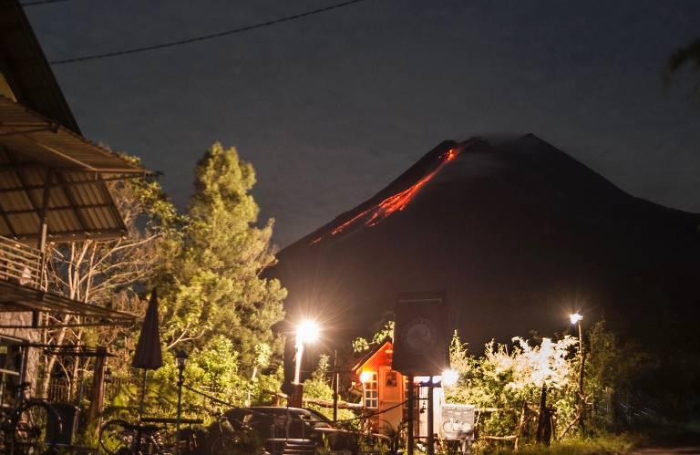 Vista de casas e árvores com vulcão em erupção ao fundo