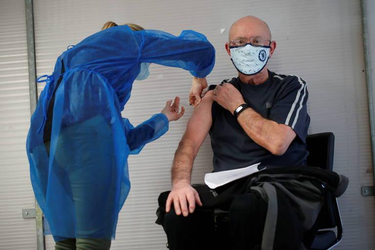 Enfermeiro de bata azul aplica injeção em homem de roupa adidas preta e máscara