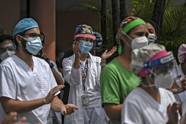 Com mascaras e proteção facial, funcionários batem palma durante ato