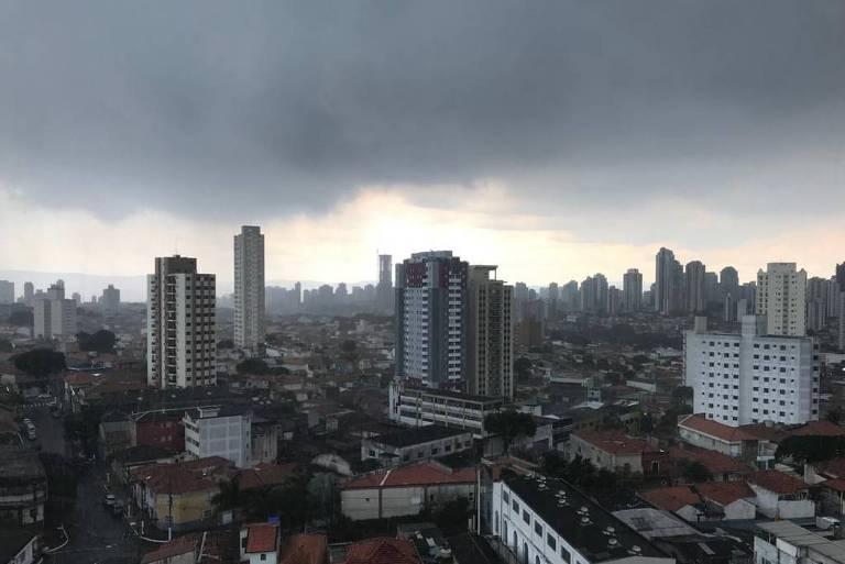 Imagem mostra céu com nuvens carregadas com prédios e casas vistos de cima