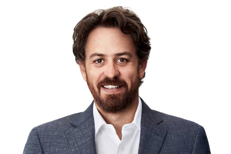 Um homem ruivo usa terno escuro e sorri para foto