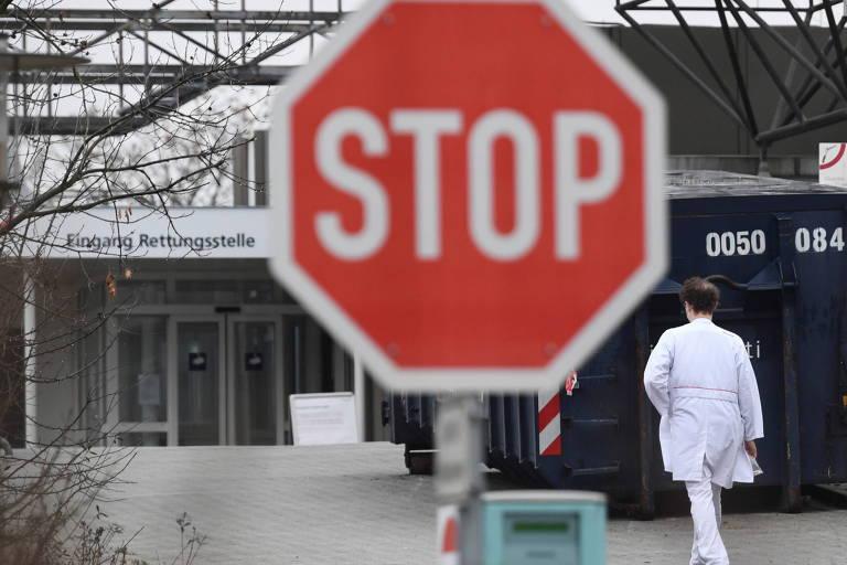Placa vermelha de Pare em primeiro plano, com pessoa de uniforme branco caminhando ao fundo em direção a porta de hospital
