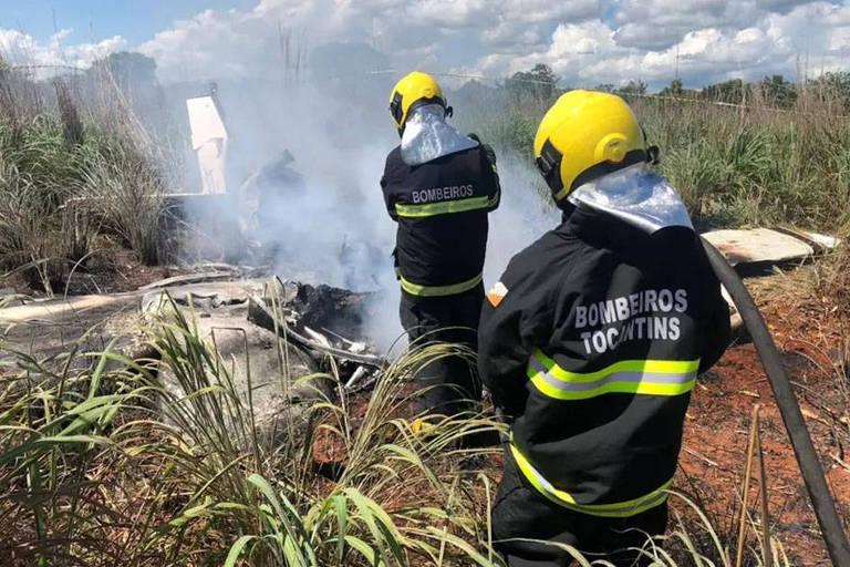 Dois bombeiros apagam fogo de avião, destruído, em matagal