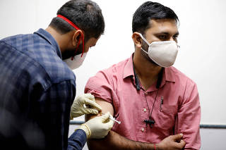 FILE PHOTO: A medic administers COVAXIN, an Indian government-backed experimental COVID-19 vaccine, to a health worker during its trials, in Ahmedabad