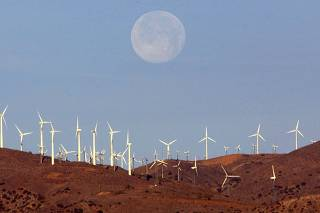 Full moon sets behind wind farm in Mojave Desert, California