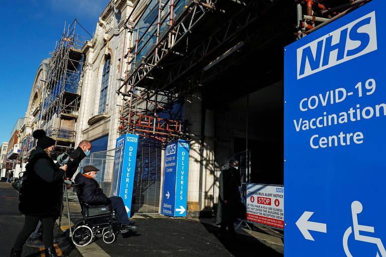 Um homem e uma mulher empurram uma cadeira de rodas para entrar em edifício que tem na frente uma grande placa azul avisando que é um centro de vacinação