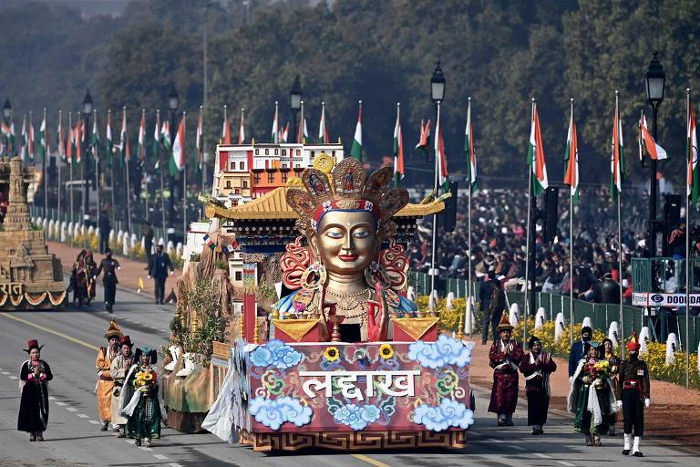 Divindade hindu retratada em carro alegórico em avenida cercada por multidão