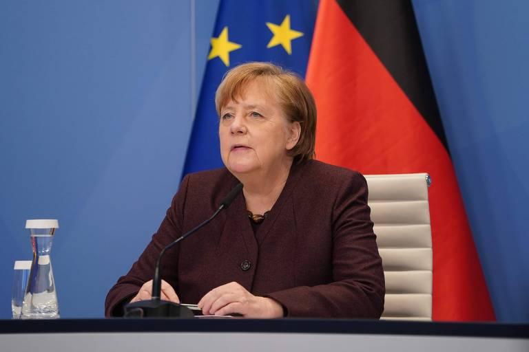 A premiê, de paletó bordô, em frente a bandeiras da Alemanha e da União Europeia