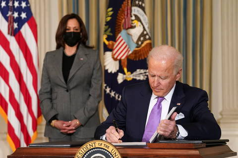 U.S. Vice President Kamala Harris watches as President Joe Biden signs executive orders on his racial equity agenda at the White House in Washington, U.S., January 26, 2021. REUTERS/Kevin Lamarque ORG XMIT: PPP WAS209