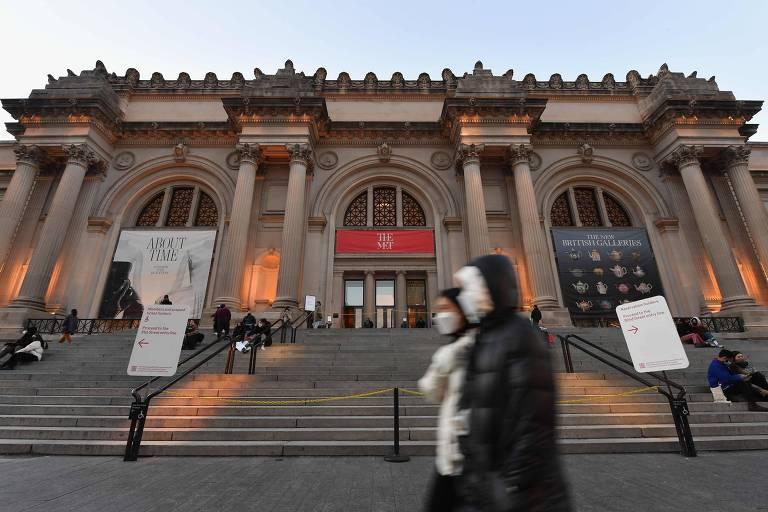 Pessoas com máscaras caminham em frente ao Met