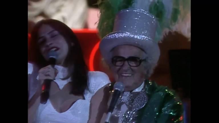 chacrinha veste cartola de glitter prateado ao apresentador seu programa de auditório