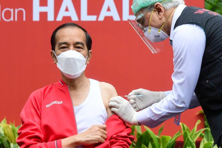 Enfermeiro aplica vacina no braço esquerdo de Widodo